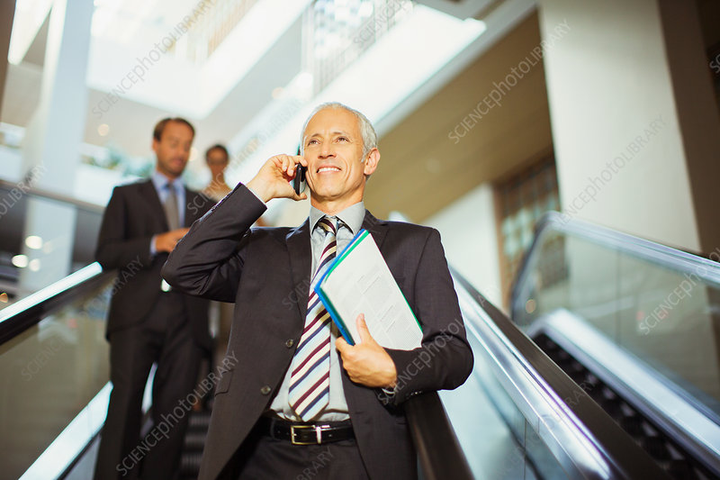 Businessman talking going down escalator