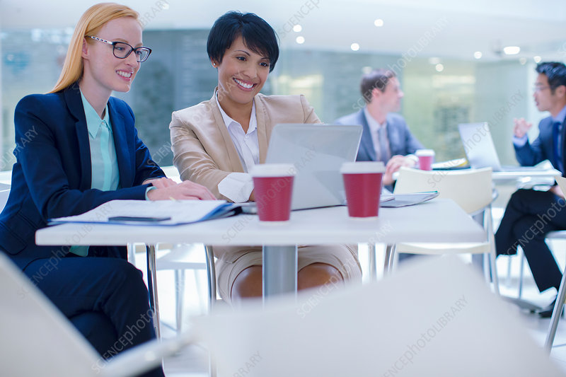 Businesswomen working on laptop at table