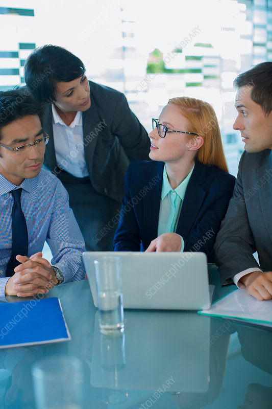 Business people gathered around laptop