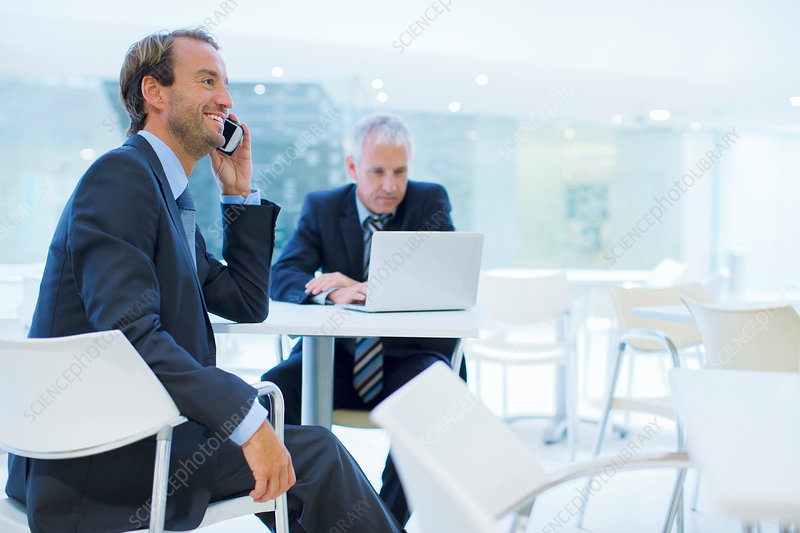 Businessman talking on call phone cafe