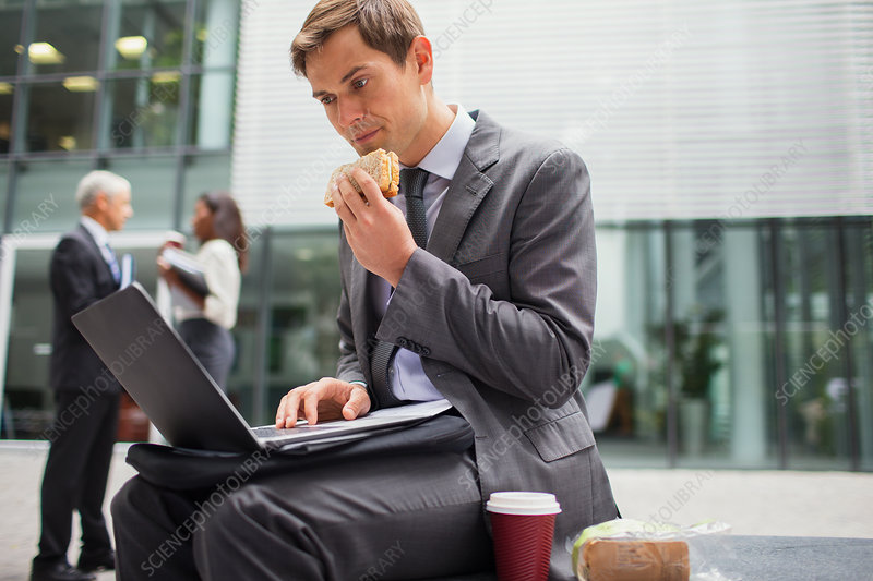 Businessman eating lunch while working