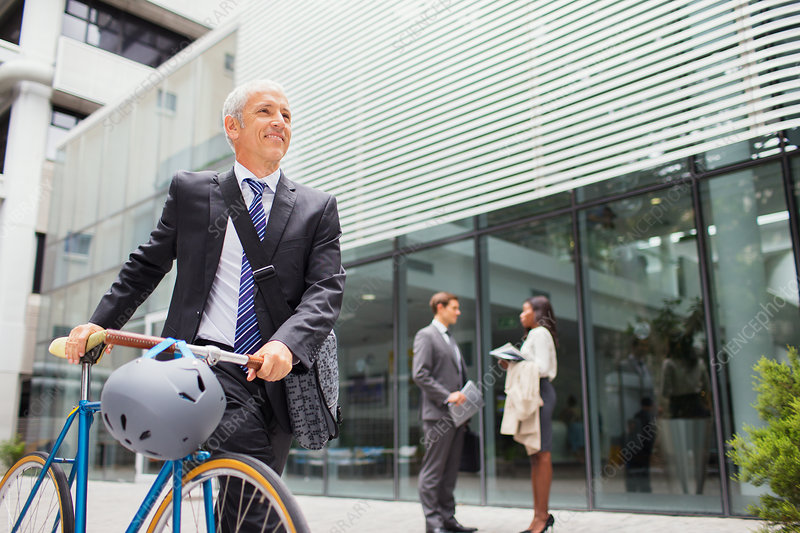 Businessman walking bicycle