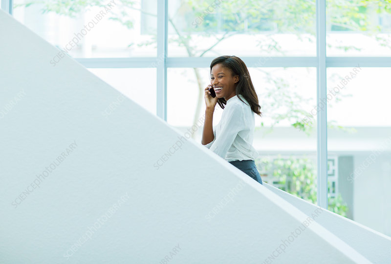 Businesswoman talking on office stairs
