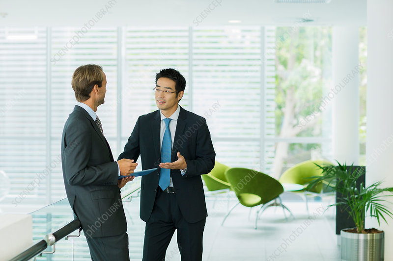 Businessmen talking in office building