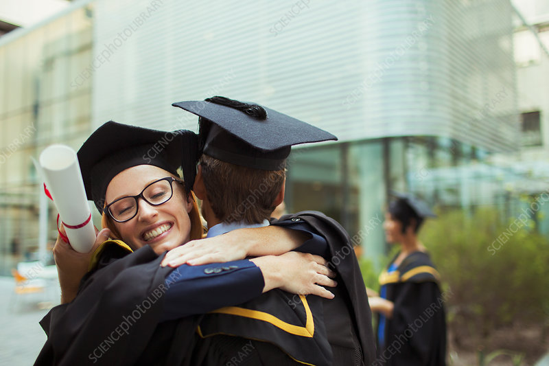 Students in cap and gown hugging