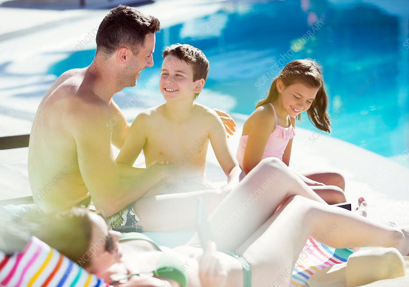 Family with two children by swimming pool