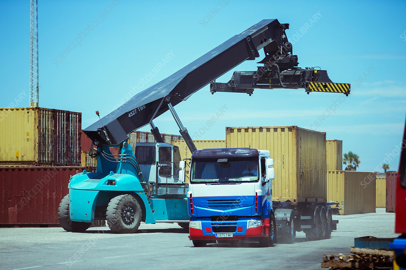 Crane near cargo container on truck