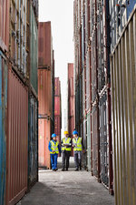 Workers talking between cargo containers