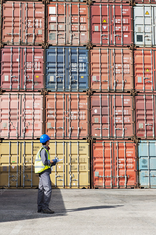Worker examining cargo containers