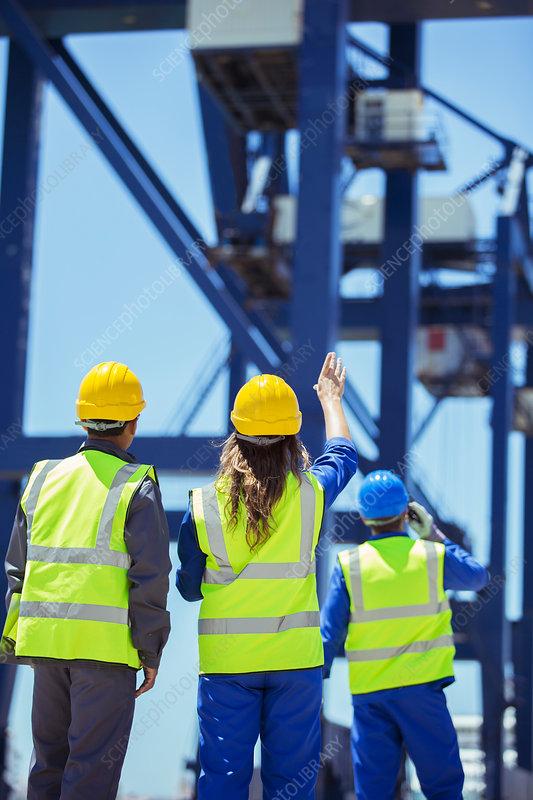 Worker and businessman examining crane