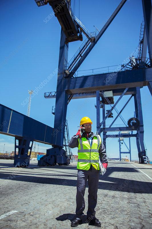 Worker talking near cargo crane