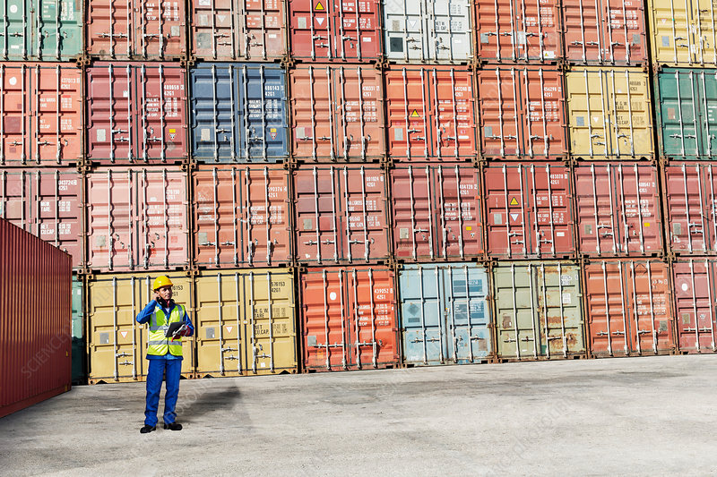 Worker standing near cargo containers