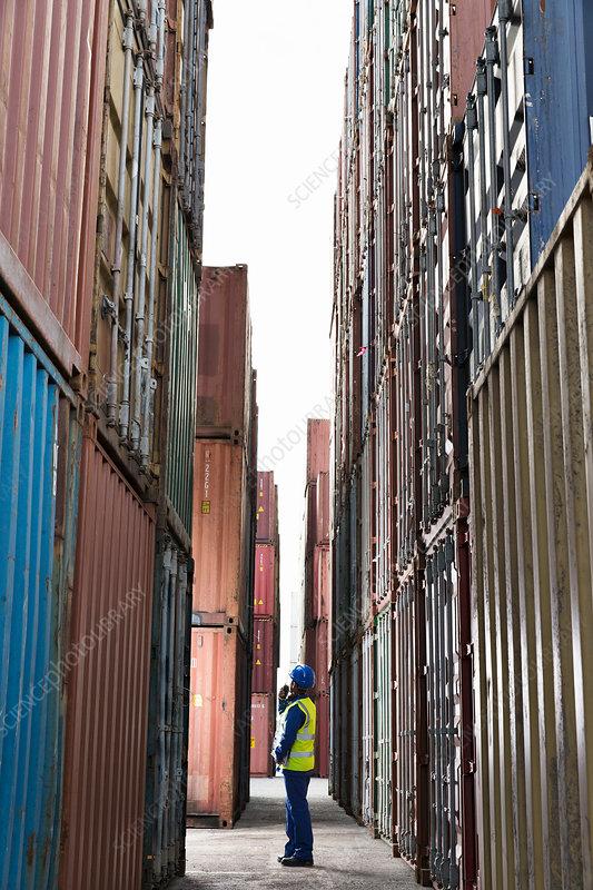 Worker standing between cargo containers