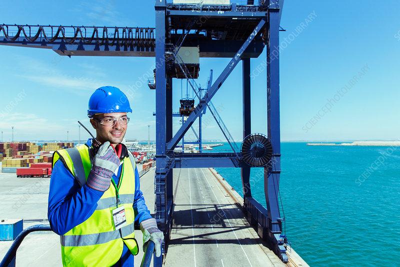 Worker using walkie-talkie at waterfront