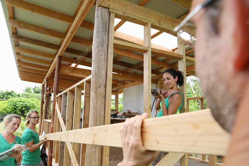 People building wooden house frame