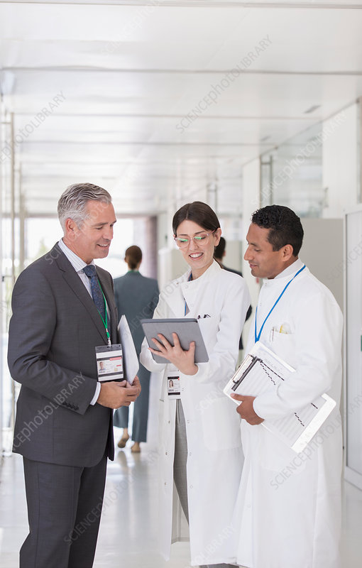 Scientists and businessman using tablet