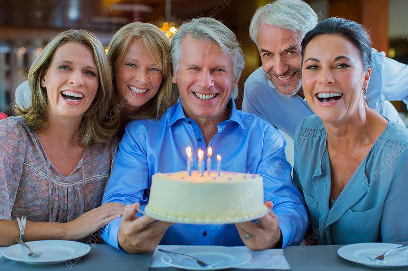 Mature men and women with birthday cake
