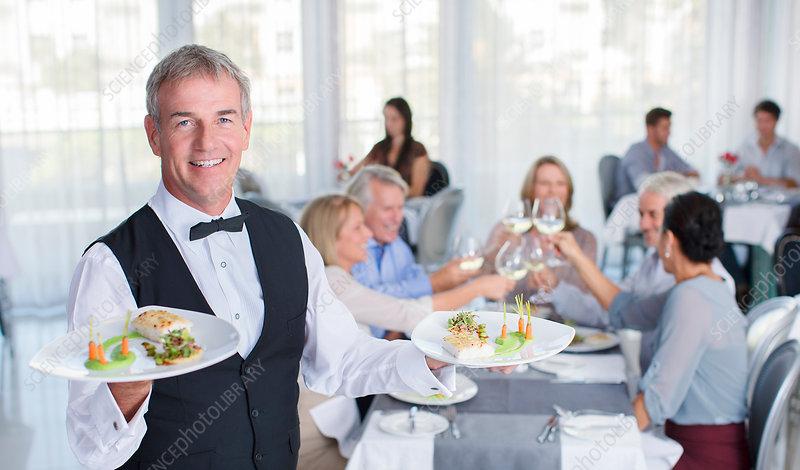 Portrait of waiter holding plate