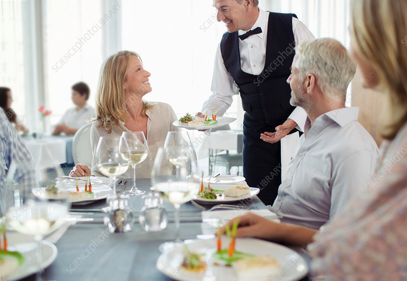 Waiter serving fancy dish to woman