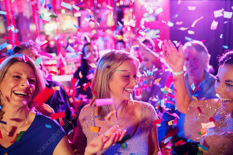 Confetti falling on mature women dancing