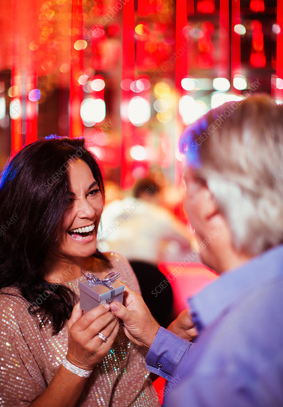 Man giving gift to smiling mature woman
