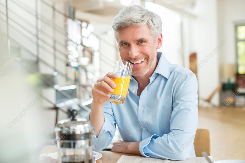 Older man drinking orange juice