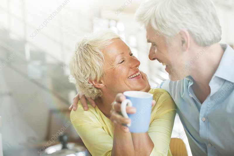 Older couple hugging with coffee cup