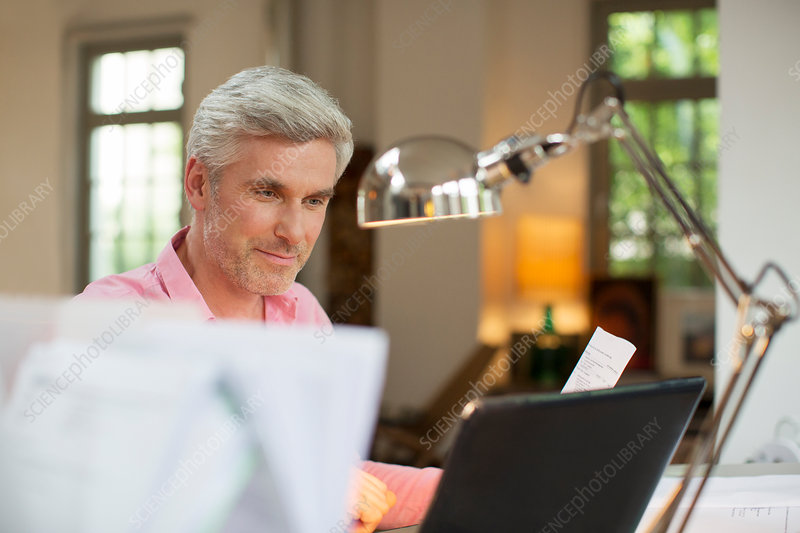 Older man using laptop in home office