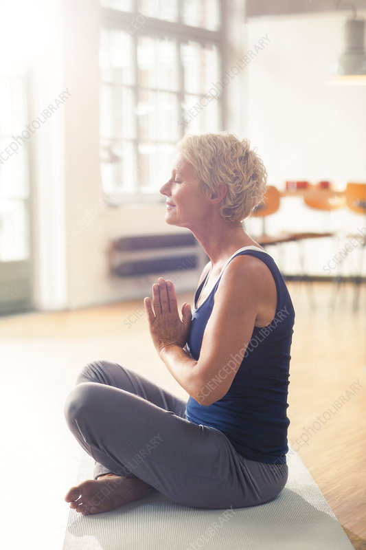 Older woman meditating on exercise mat