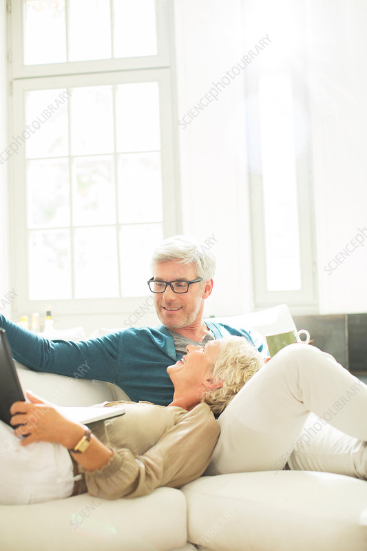 Older couple relaxing on living room sofa