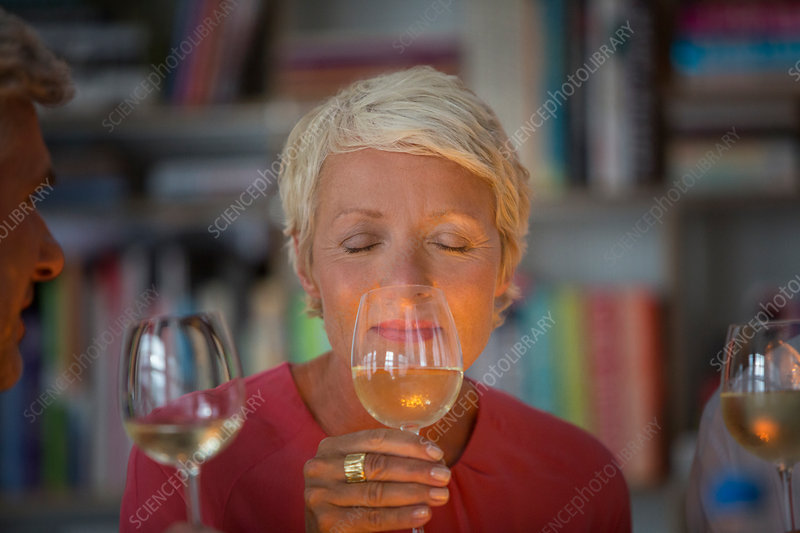 Older woman smelling white wine