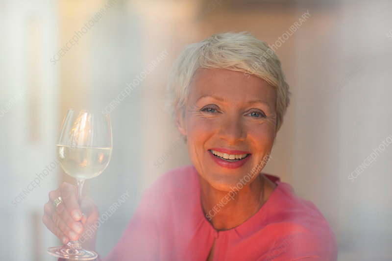 Older woman drinking glass of white wine