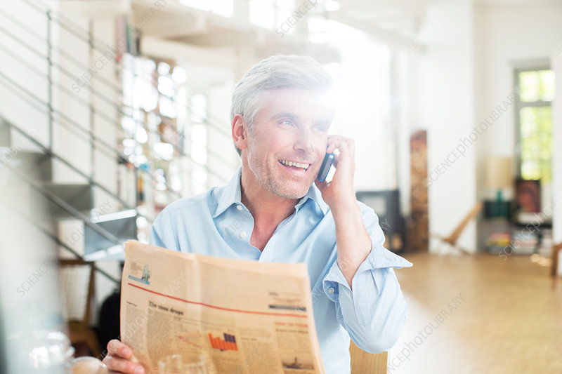 Older man talking with newspaper