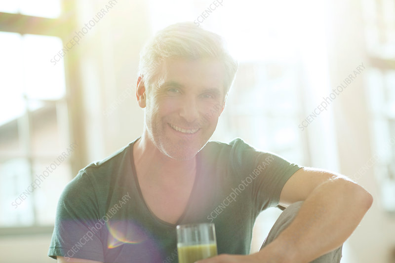 Older man drinking glass of juice