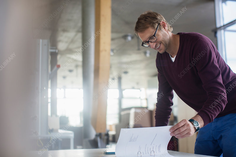 Businessman reading paperwork in office