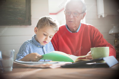 Boy reading with grandfather at table