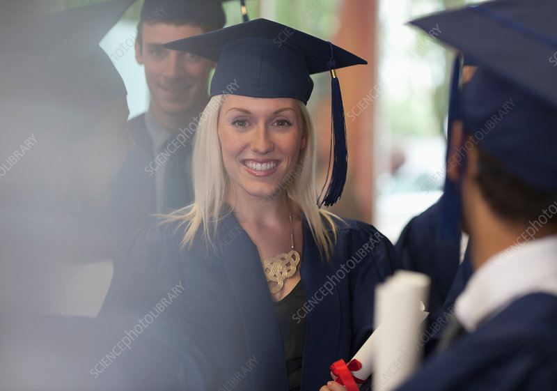 Student smiling in graduation clothes