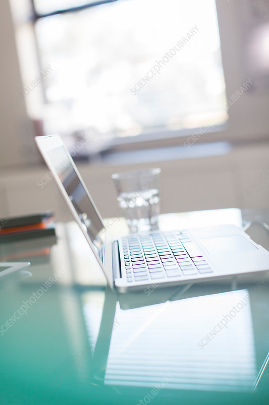 Open laptop and glass of water