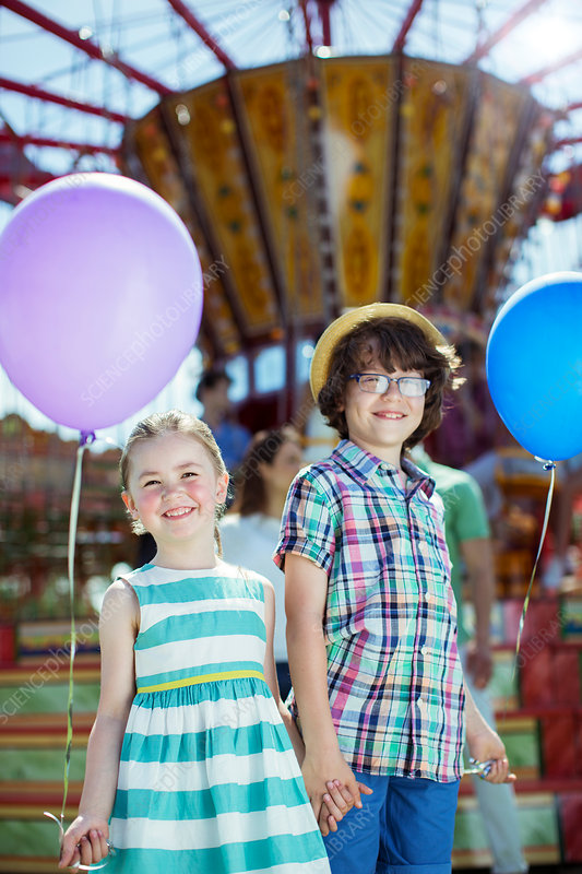Boy and girl holding balloons