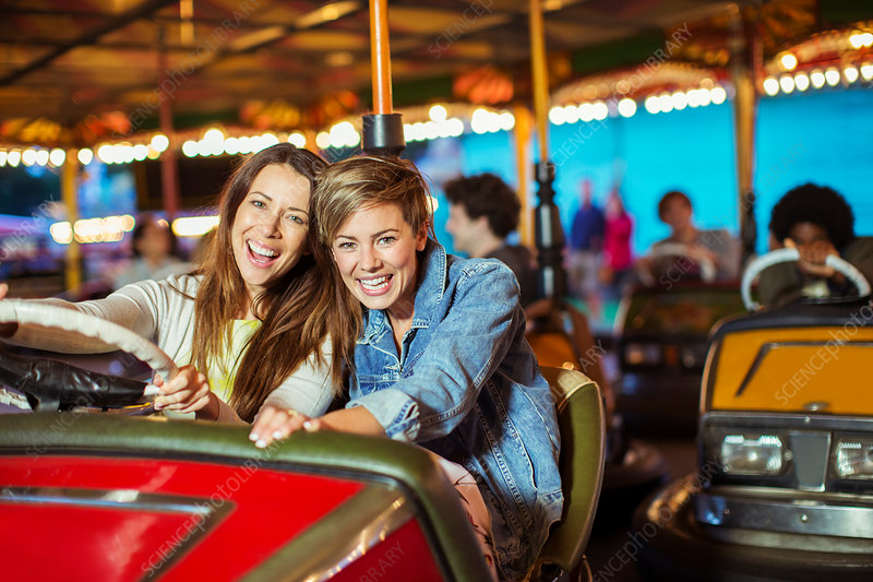 Two cheerful women on bumper car ride