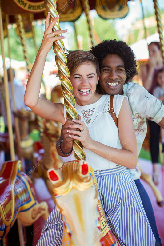 Young multiracial couple on carousel