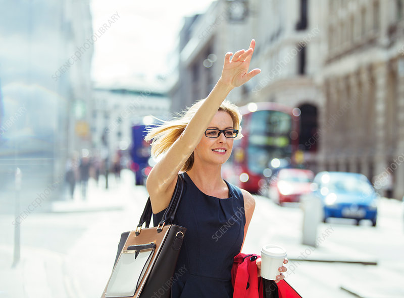 Businesswoman hailing taxi in city
