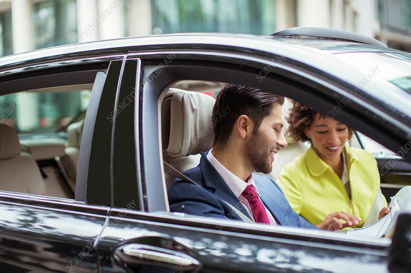 Business people reading paperwork in car