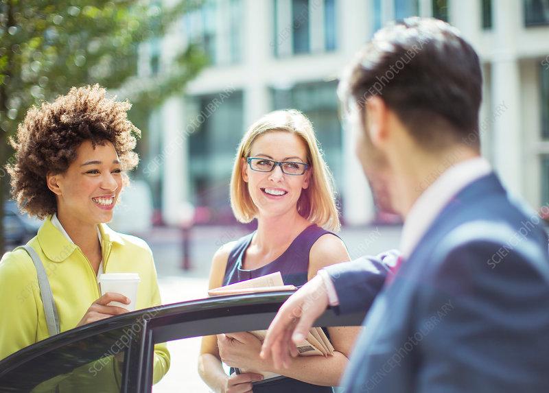 Business people talking near car