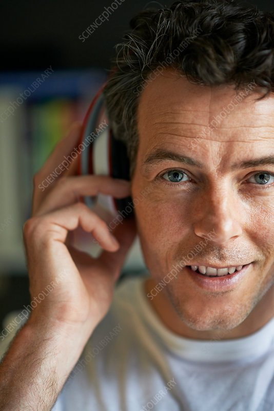Smiling man with headphones on, close up