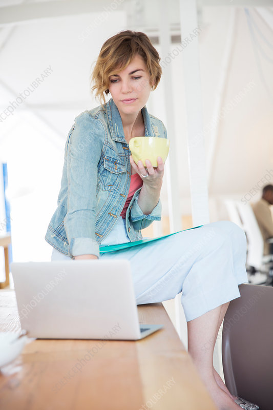 Office worker with coffee using laptop