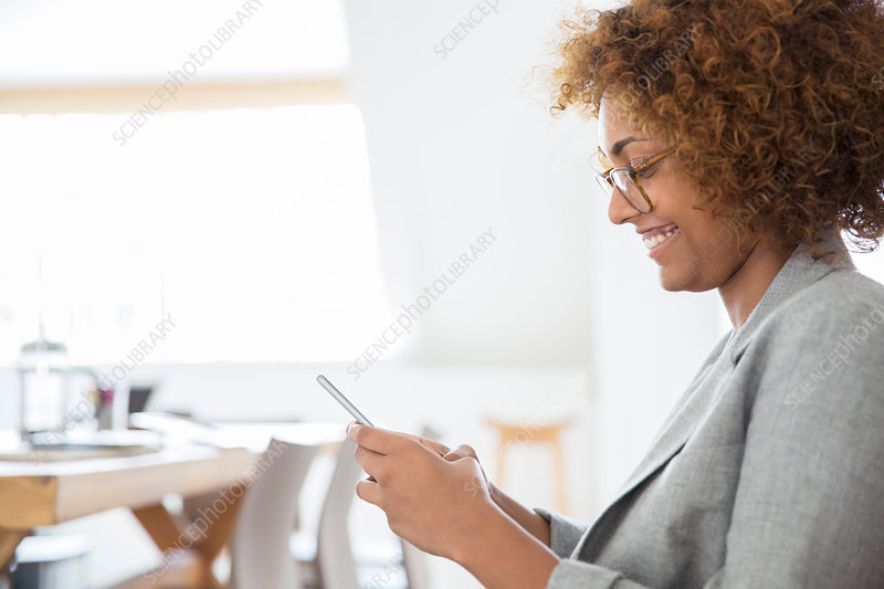 Woman using smart phone and smiling