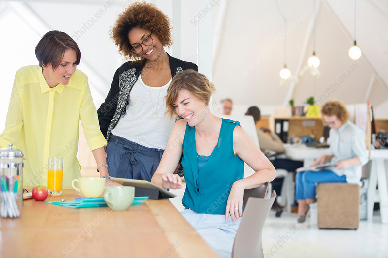 Women looking at tablet and smiling
