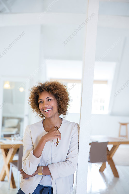 Woman leaning on column and smiling