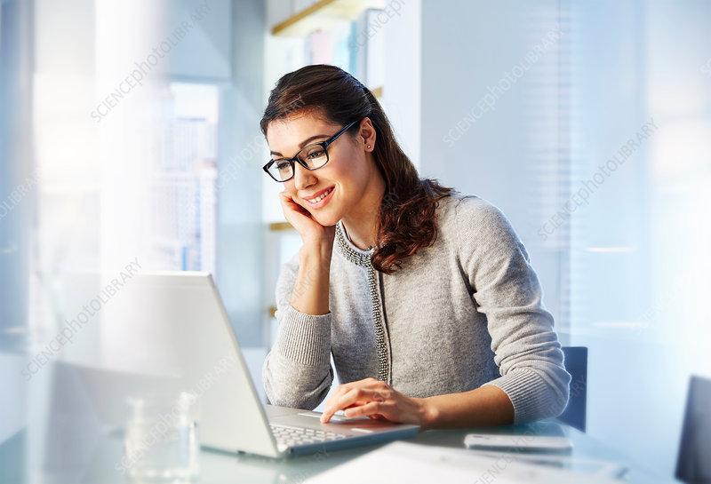 Female office worker sitting using laptop